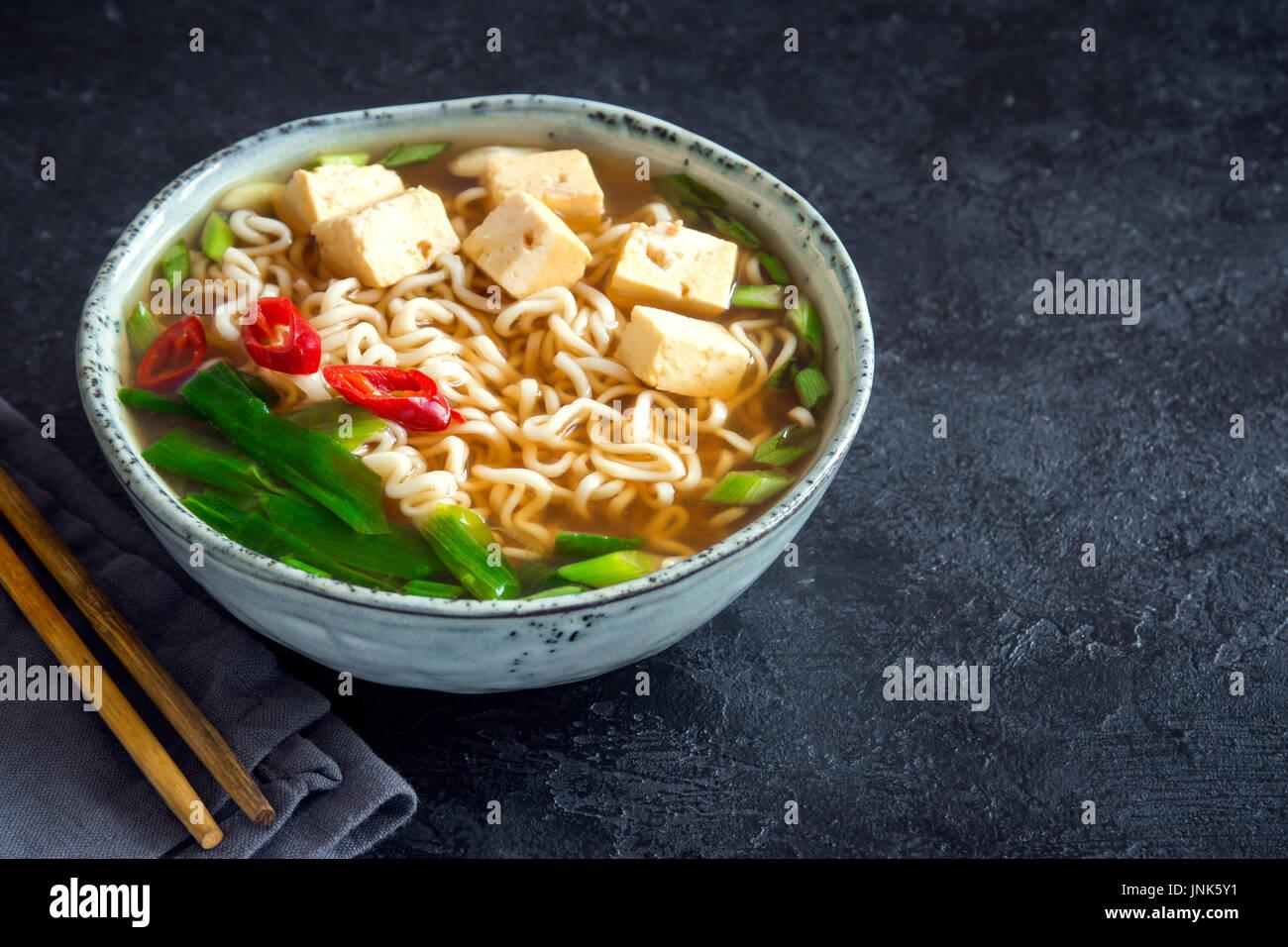 Soupe ramen japonais avec le tofu sur pierre sombre arrière-plan. La soupe miso avec des nouilles ramen et le tofu dans un bol en céramique, asiatique traditionnelle. Photo Stock