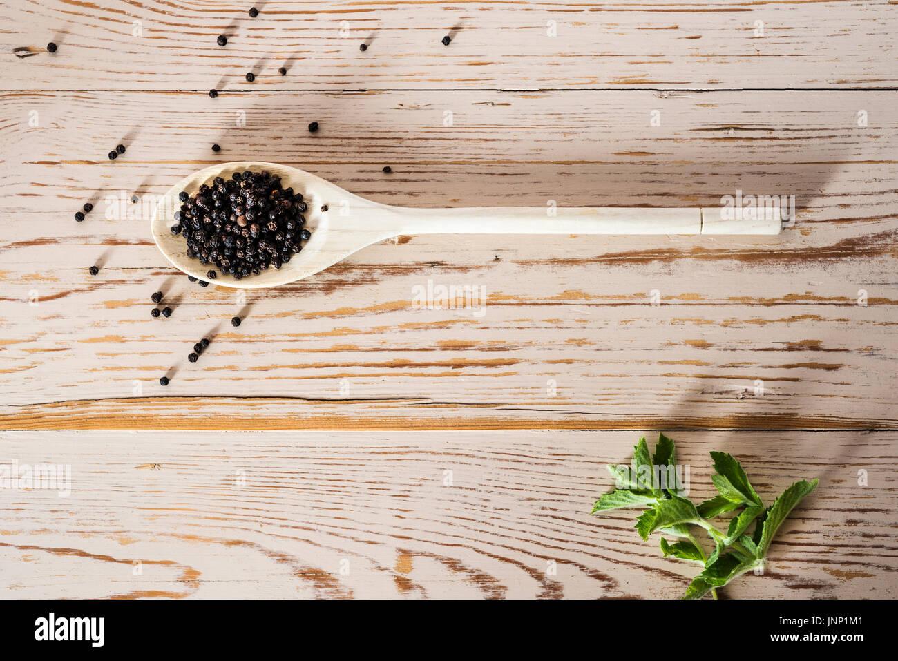 Coup de frais généraux de cuillère en bois sur la table en détresse, avec le poivre noir. Photo Stock