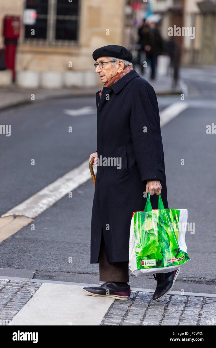 France - 5 mars 2016   homme plus âgé en manteau, écharpe et béret de  traverser la rue avec des sacs de magasinage sur la rue Saint-Antoine, dans  le Marais, ... 379f307a4a9