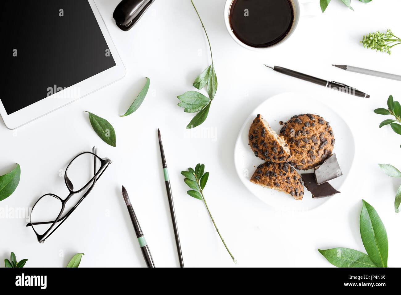 Vue de dessus de tablette numérique, les cookies et les fournitures de bureau isolé sur blanc, concept de communication sans fil Photo Stock