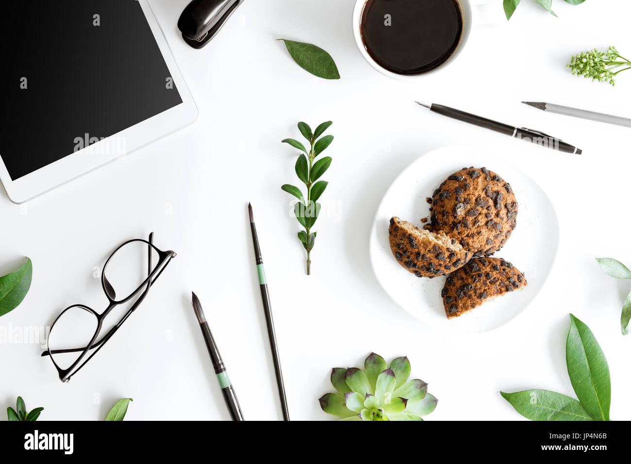 Vue de dessus de tablette numérique, les cookies et les fournitures de bureau isolé sur blanc, concept de communication Banque D'Images