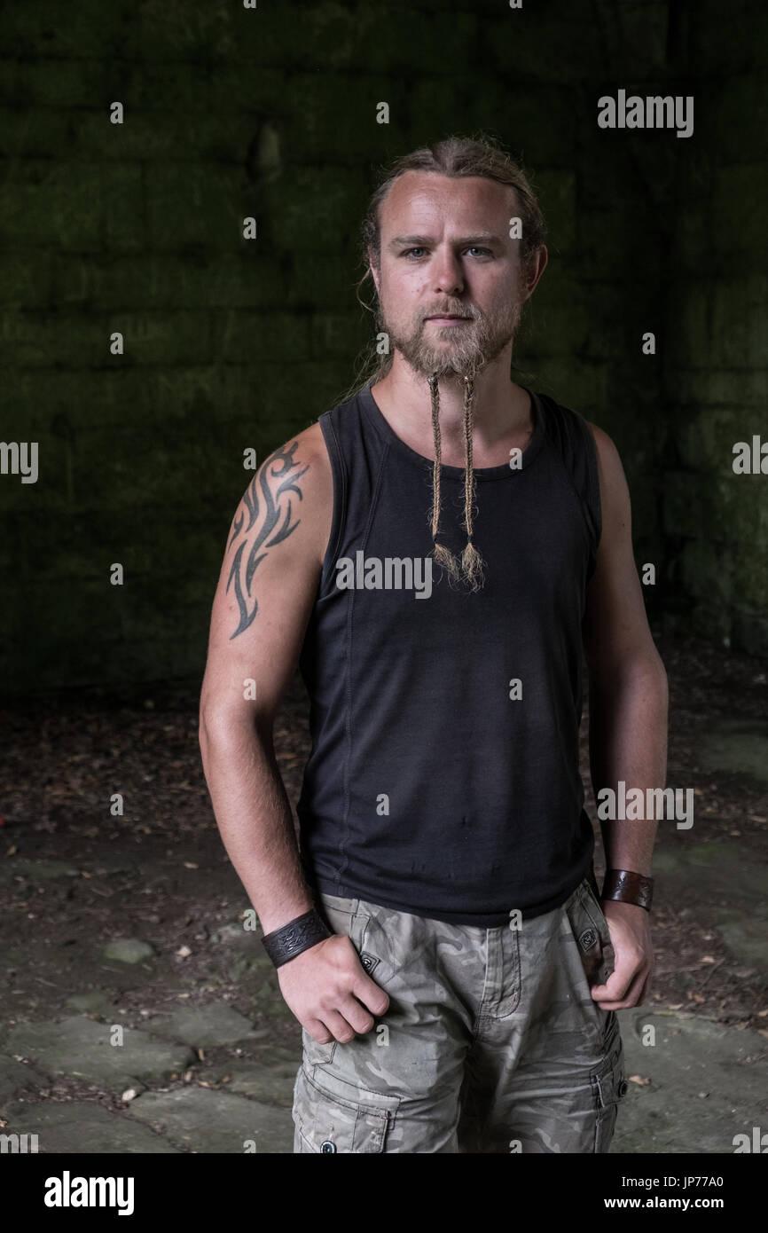 Soldat guerrier médiéval reconstitution d\u0027un jeune homme aux cheveux longs, barbe  tressée et tatouage