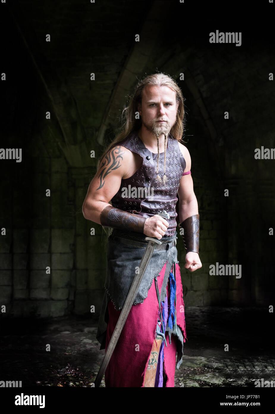 La reconstitution médiévale viking warrior soldat, jeune homme avec de  longs cheveux tressés, barbe et portant des tatouages viking
