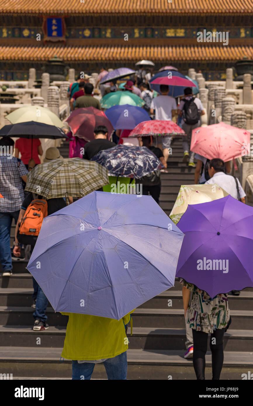 Les touristes détenteurs de parasols colorés de grimper les escaliers à la salle de l'harmonie suprême dans la Cité Interdite, Pékin, Chine Photo Stock