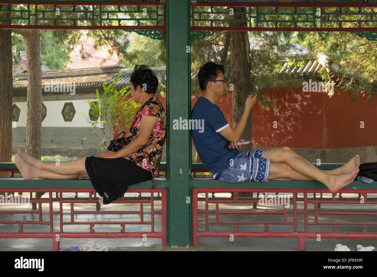 Deux touristes chinois en faisant une pause en visitant le palais d'été assis sur la rambarde du Long Couloir Photo Stock