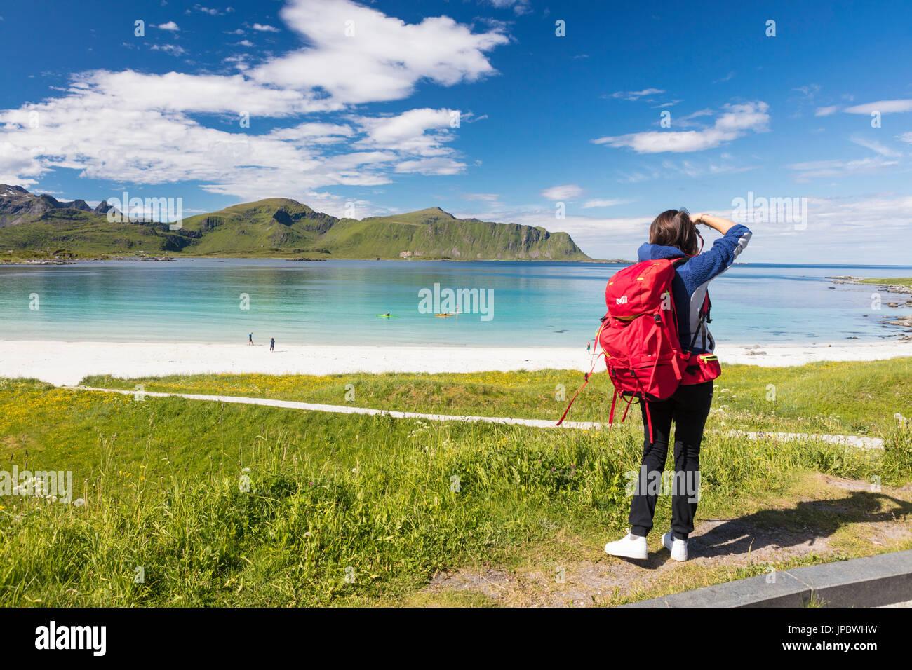 Photographe en action dans les verts pâturages entourés par une mer turquoise et sable fin Ramberg Lofoten, Norvège Europe Photo Stock