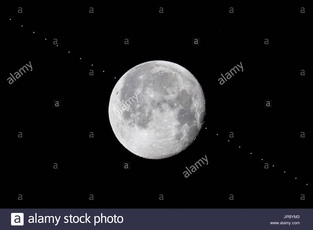 La Station spatiale internationale ISS en passant en face de la pleine lune, l'exposition multi-image, diverses étapes de progrès, la trajectoire de vol de l'orbite des satellites Photo Stock