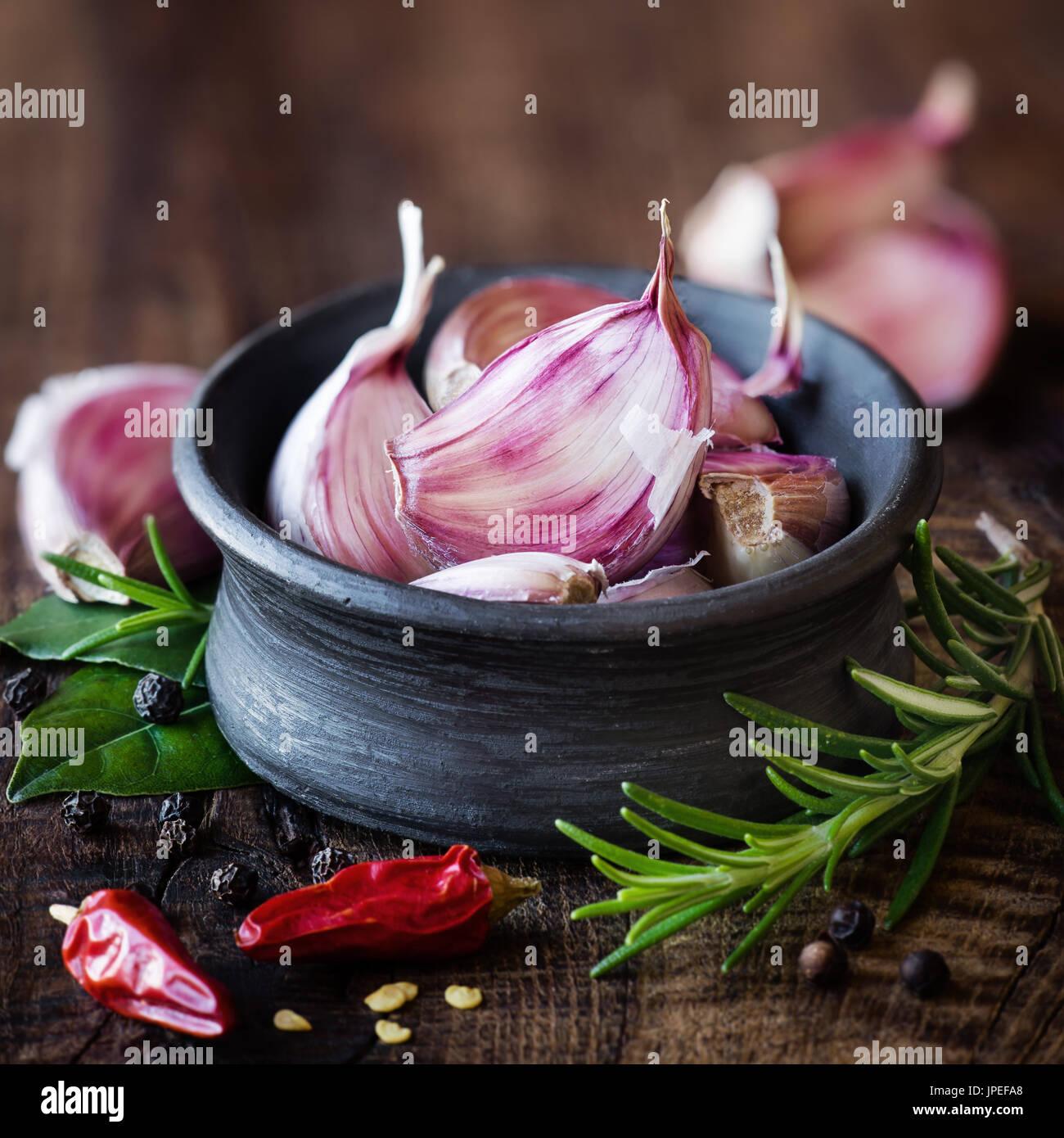 Gousses d carlic pourpre noir dans un bol avec le romarin, le laurier, le poivre noir et de piment sur fond de bois rustique foncé. Avec beaucoup copier savs Photo Stock