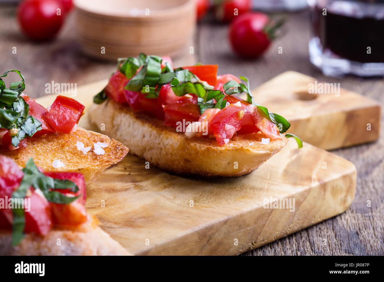 Bruschetta Tomate et basilic avec du pain à l'ail grillé, apéritif italien traditionnel sur planche à découper en bois rustique Photo Stock