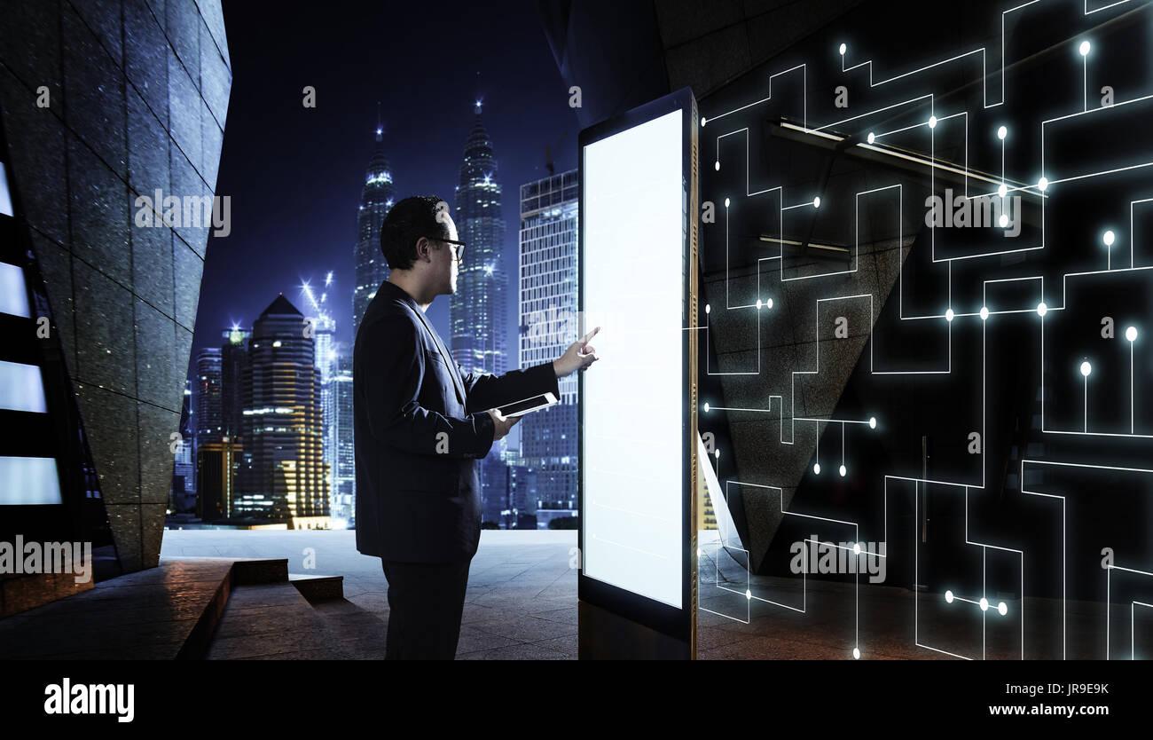 Smart businessman de toucher l'écran pour rechercher l'information de réseau de communication intelligente des choses . Scène de nuit avec l'arrière-plan la ville moderne Photo Stock