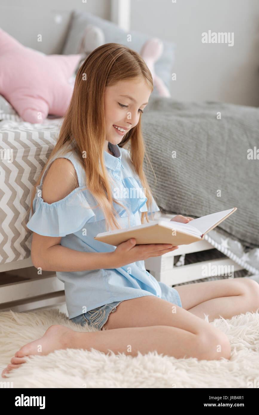 Jeune femme intelligente lecture dans la chambre Photo Stock