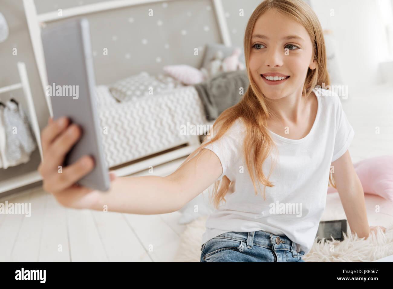 Petite fille excité en tenant vos autoportraits dans sa chambre à coucher Photo Stock