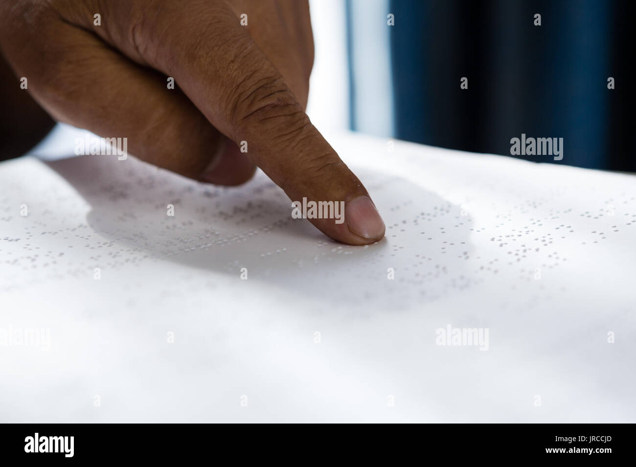 La main coupée sur senior man reading livre en braille en maison de retraite f960b1125e1