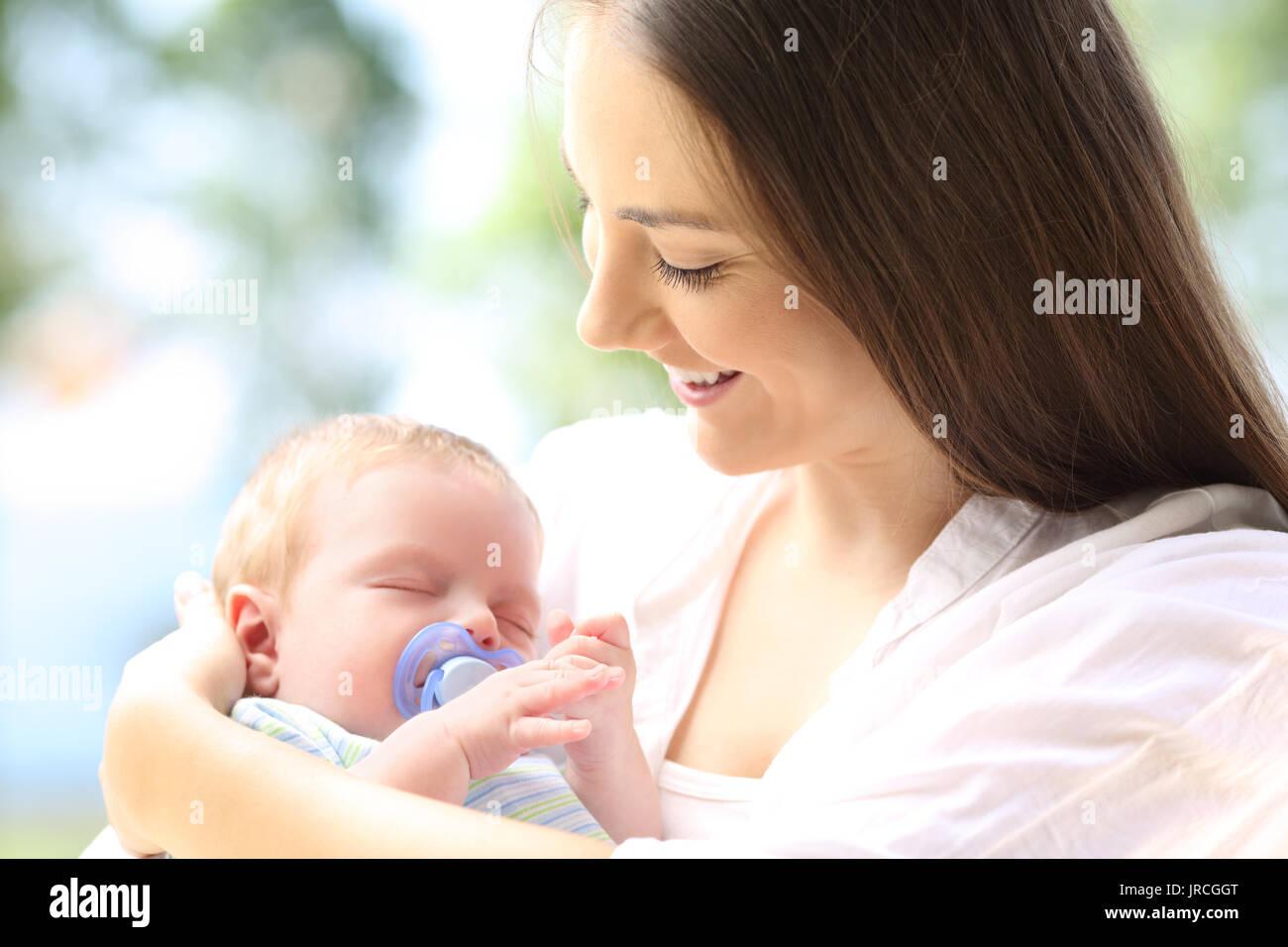 Fière mère regardant son bébé dormir en plein air Banque D'Images