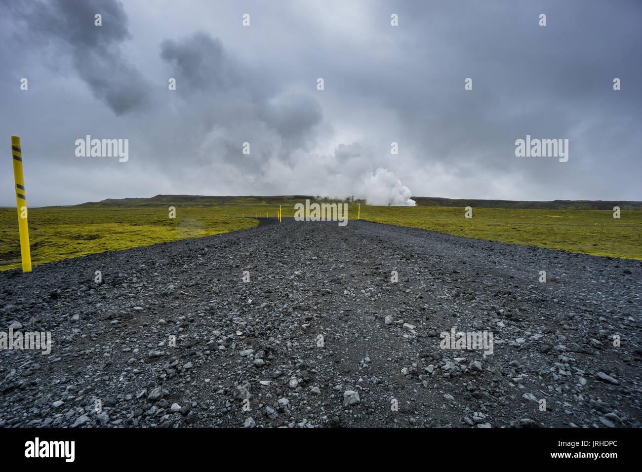 Islande - route solitaire à l'énergie géothermique et de mousse verte champ de lave Photo Stock