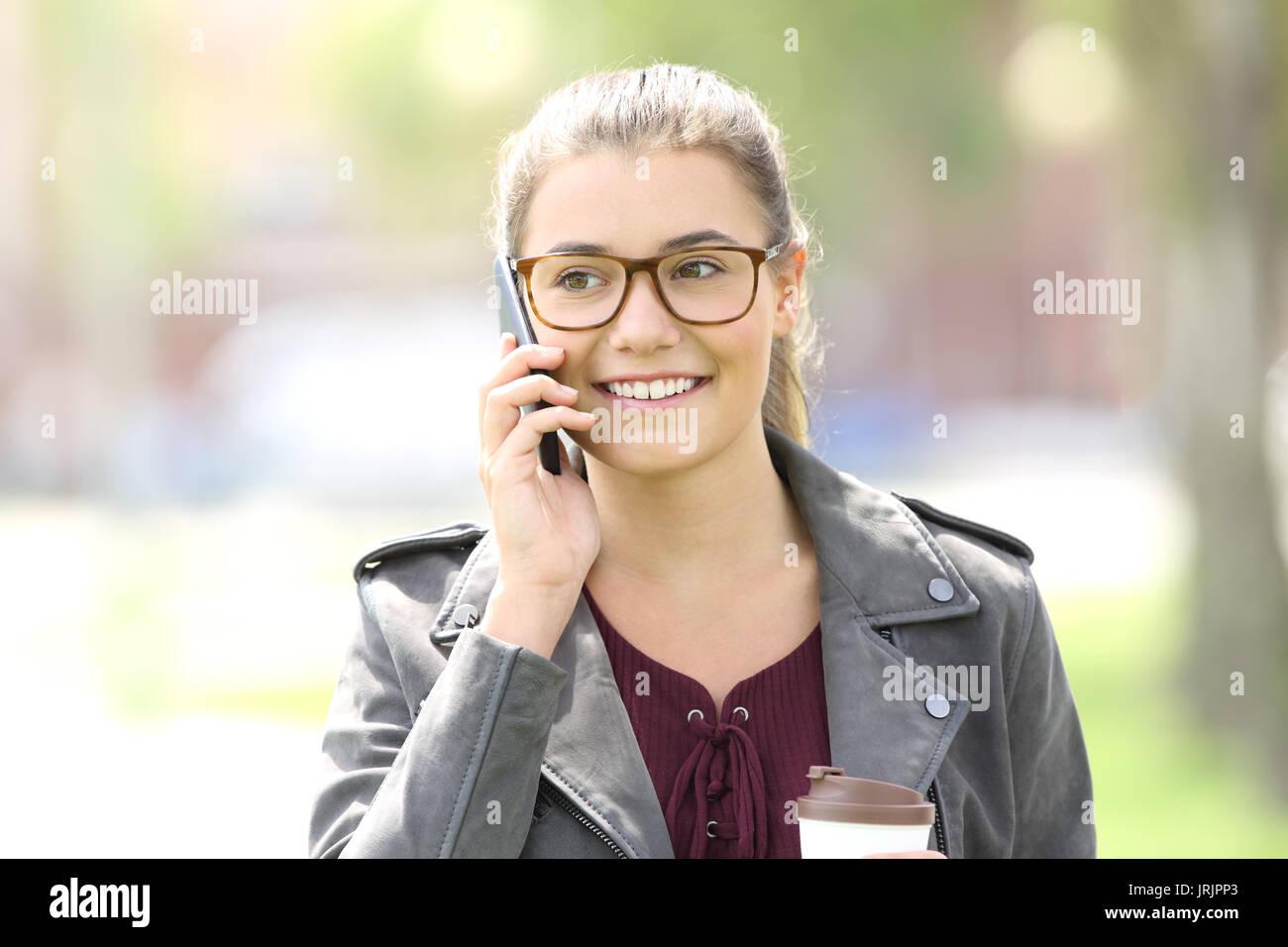 Vue frontale d'une fashion girl walking towards camera et d'appel sur téléphone mobile Banque D'Images