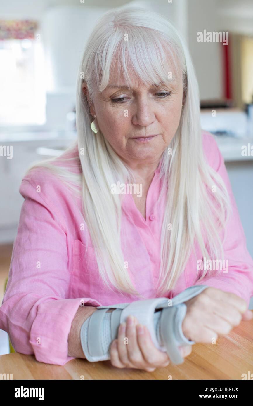 Mature femme souffrant de blessures au poignet à la maison Photo Stock