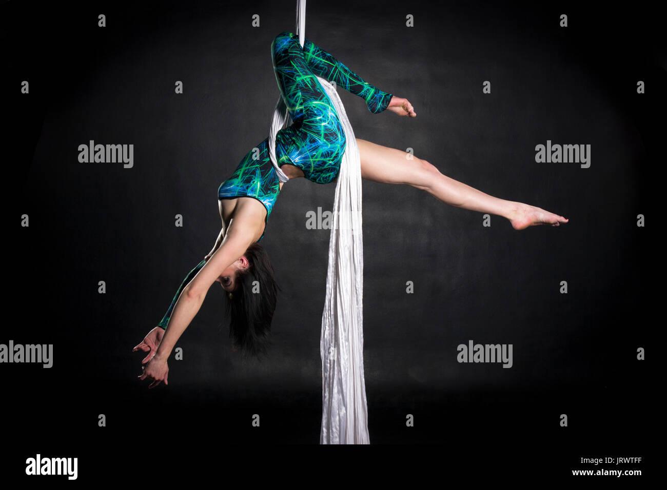 Aerialist woman doing some la souplesse et la force des tours sur la soie Photo Stock