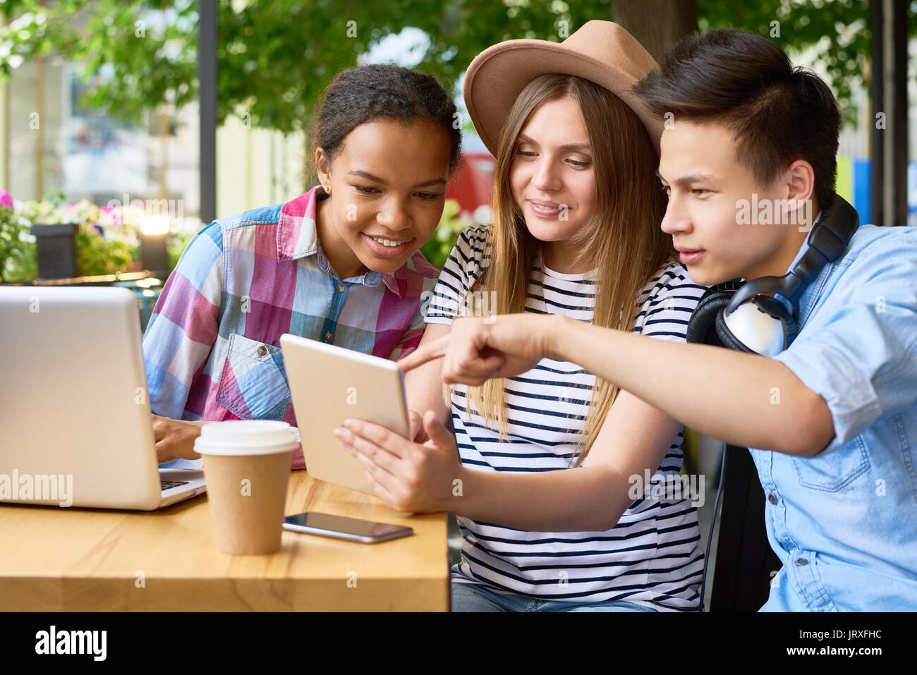 Les jeunes à l'aide de dispositifs modernes de Cafe Photo Stock