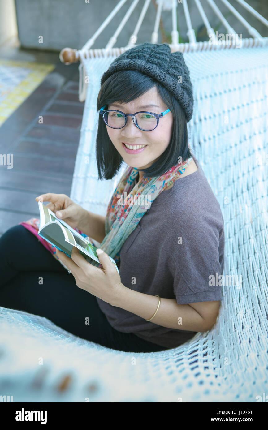 Dents sourire de femme asiatique reader livre de poche et dans la main Photo Stock