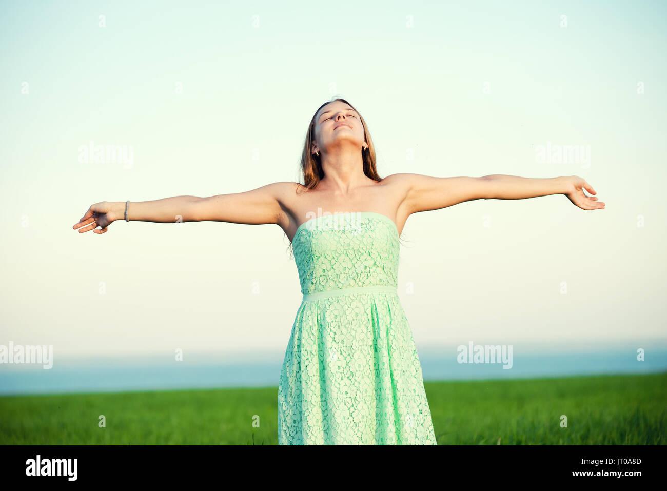 Bonheur femme rester extérieur sous la lumière du soleil de coucher du soleil Photo Stock
