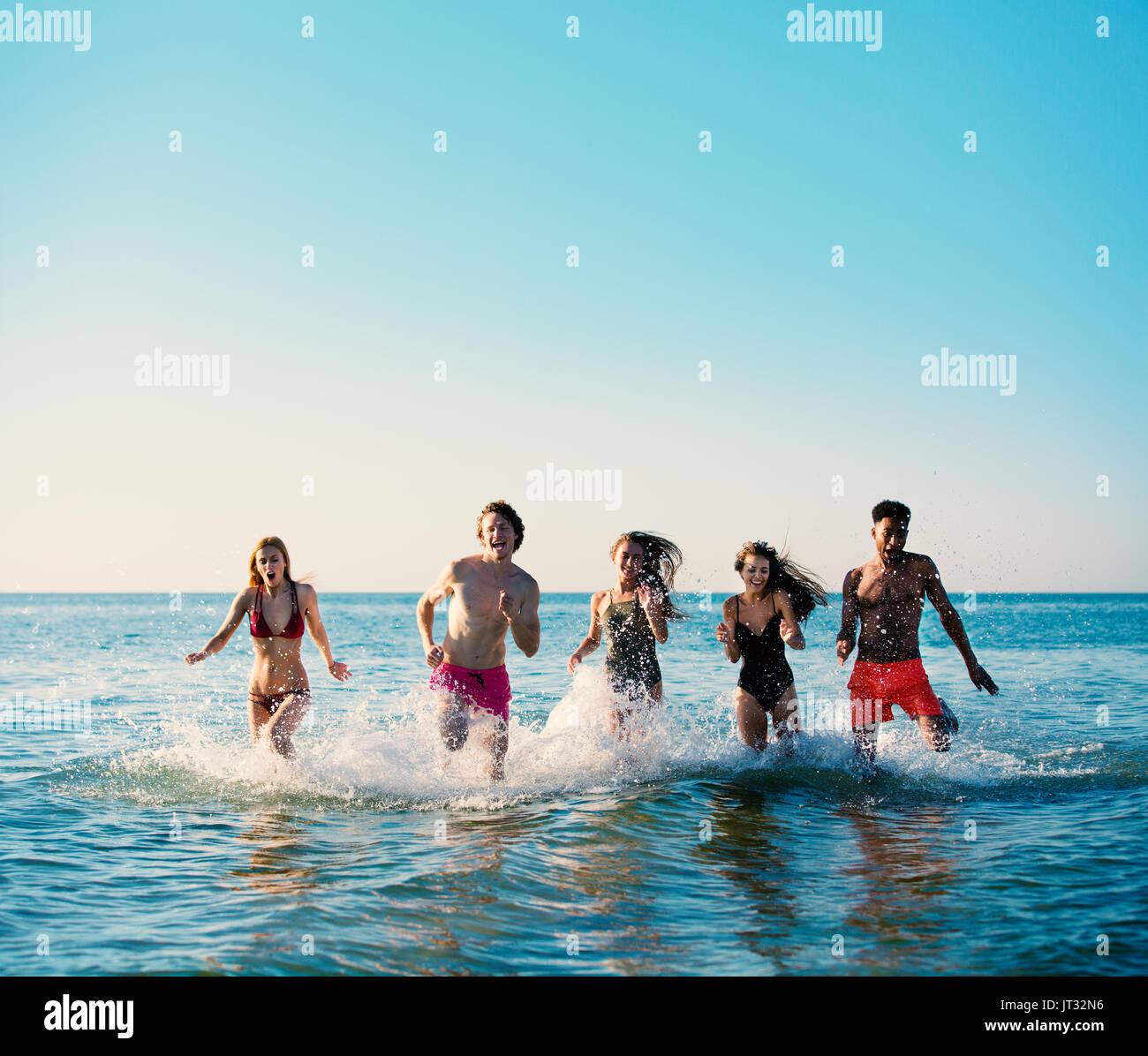 Groupe d'amis s'exécuter dans la mer. Concept d'été Photo Stock