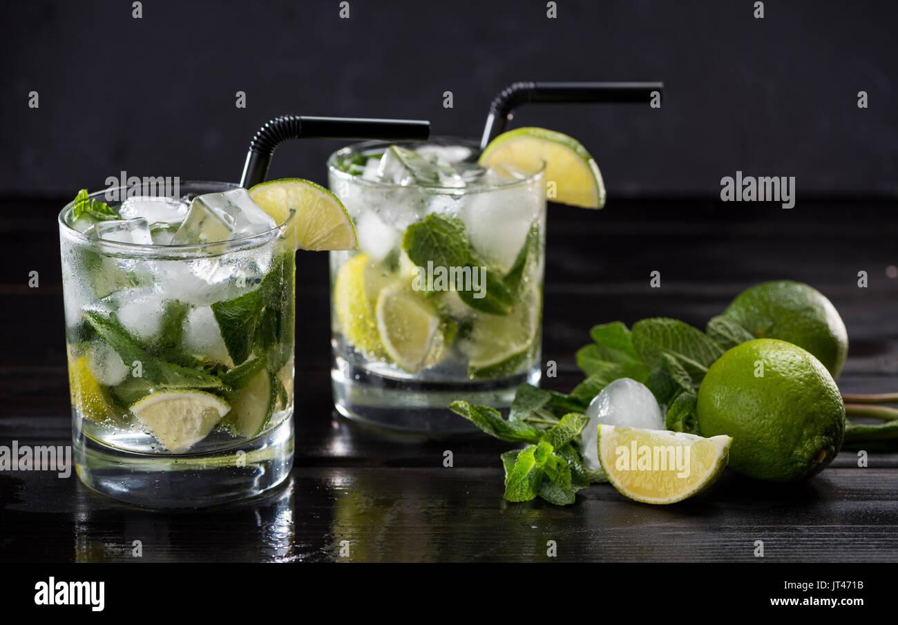 Vue rapprochée de mojito cocktail dans des verres, Menthe et citron vert sur noir, cocktails concept Photo Stock