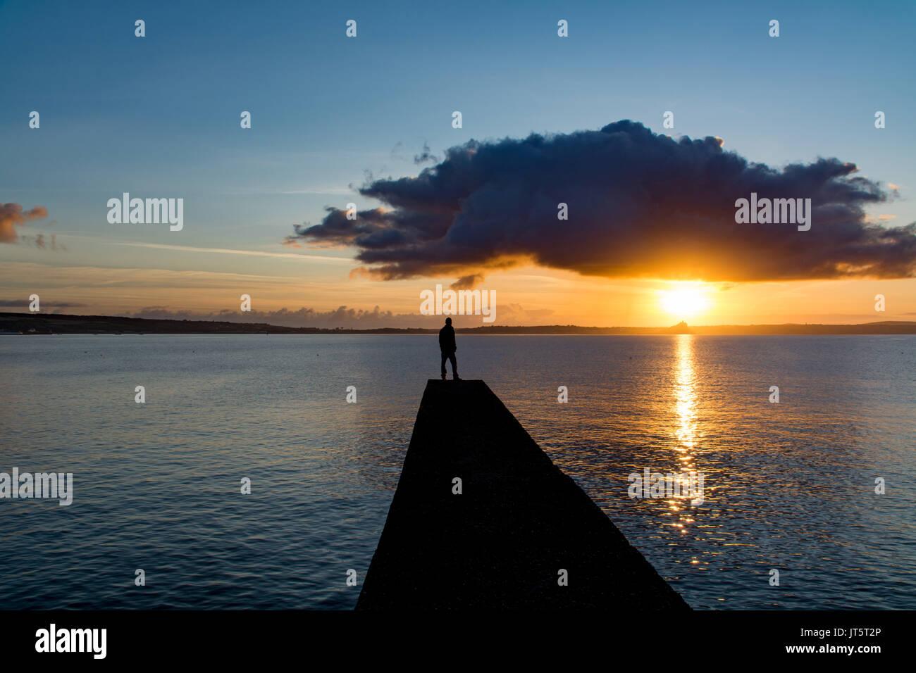 L'homme sur la jetée à la recherche au lever du soleil sous un nuage sombre Photo Stock