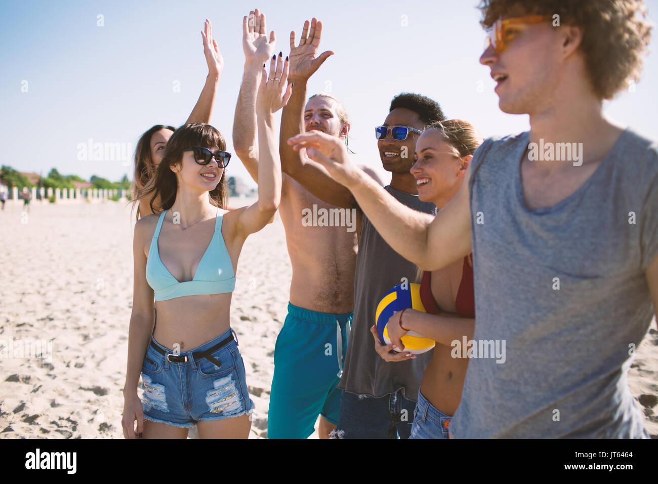 Groupe d'amis jouant au beach-volley sur la plage Photo Stock