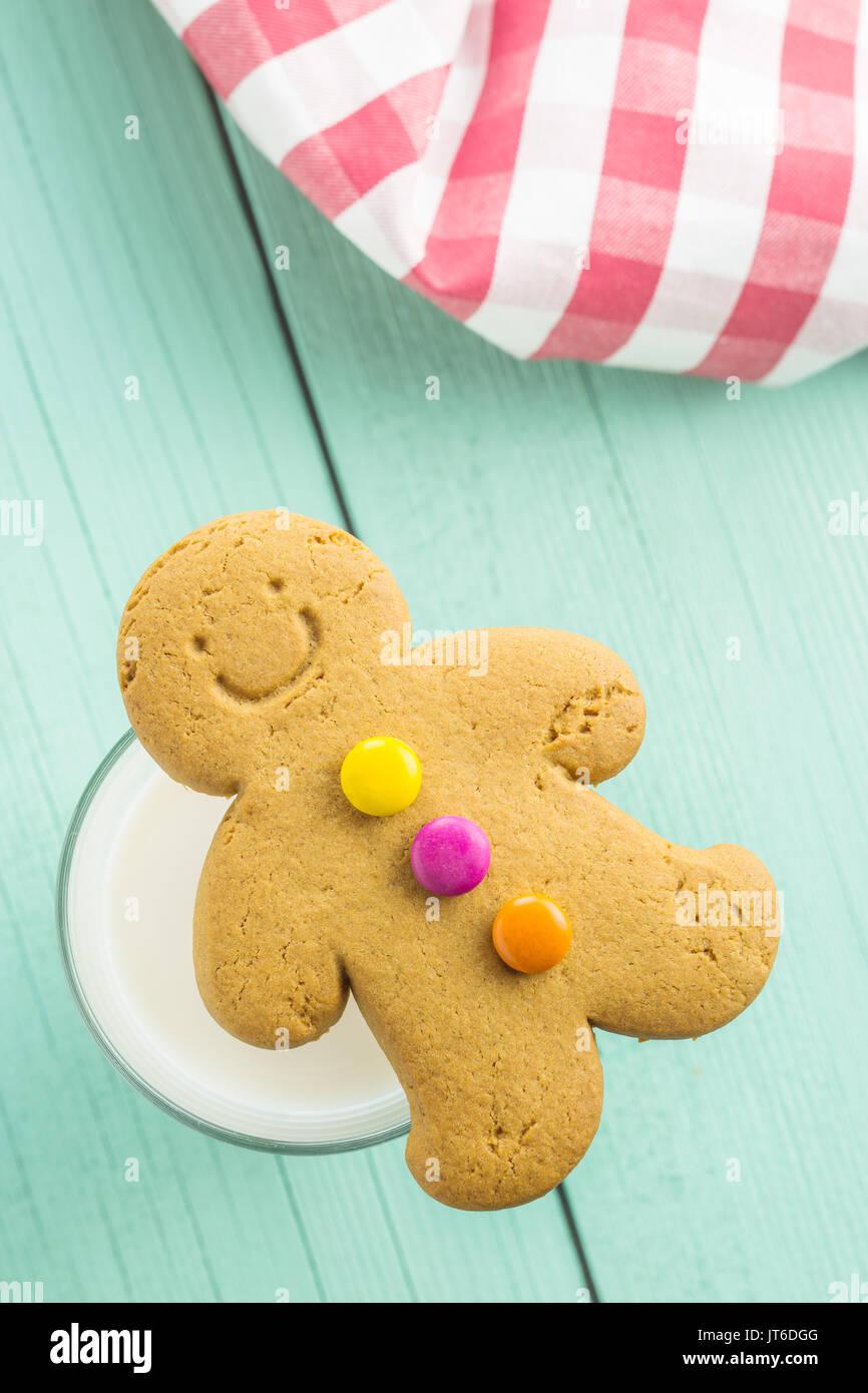 Sweet Gingerbread Man et verre de lait sur la table en bois. D'épices de Noël. Photo Stock