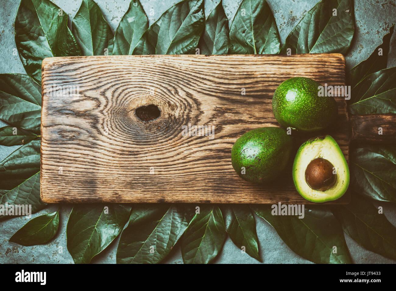 Arrière-plan de l'alimentation, de l'avocat avocat frais avec les feuilles des arbres et planche à découper en bois. Concept de récolte, le guacamole ingrédients. Gras sain, omega 3. La moitié o Photo Stock
