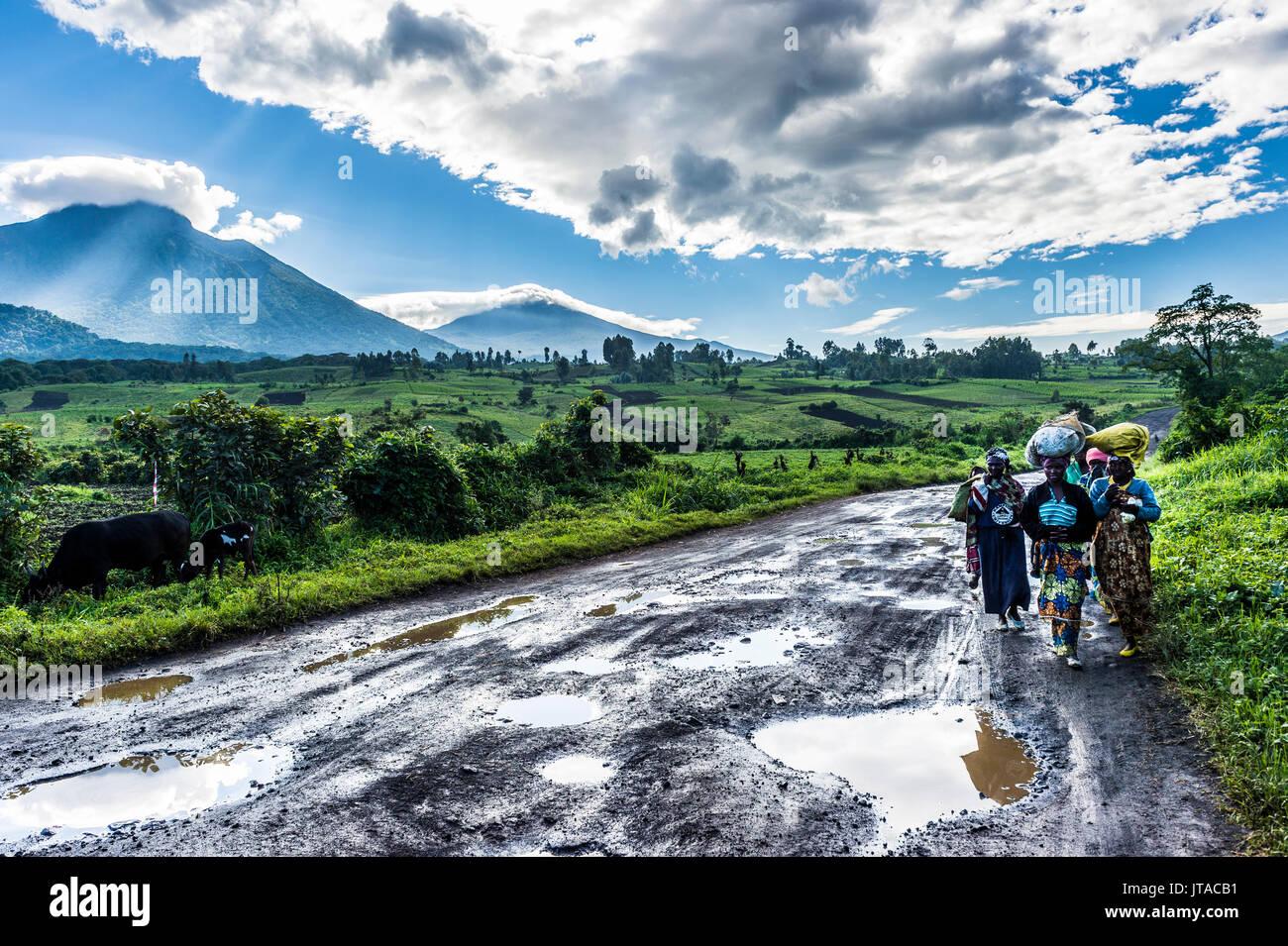 Les femmes locales transportant des marchandises sur leur tête avec la chaîne de montagnes volcaniques du Parc National des Virunga derrière, après la pluie, la République démocratique du Photo Stock