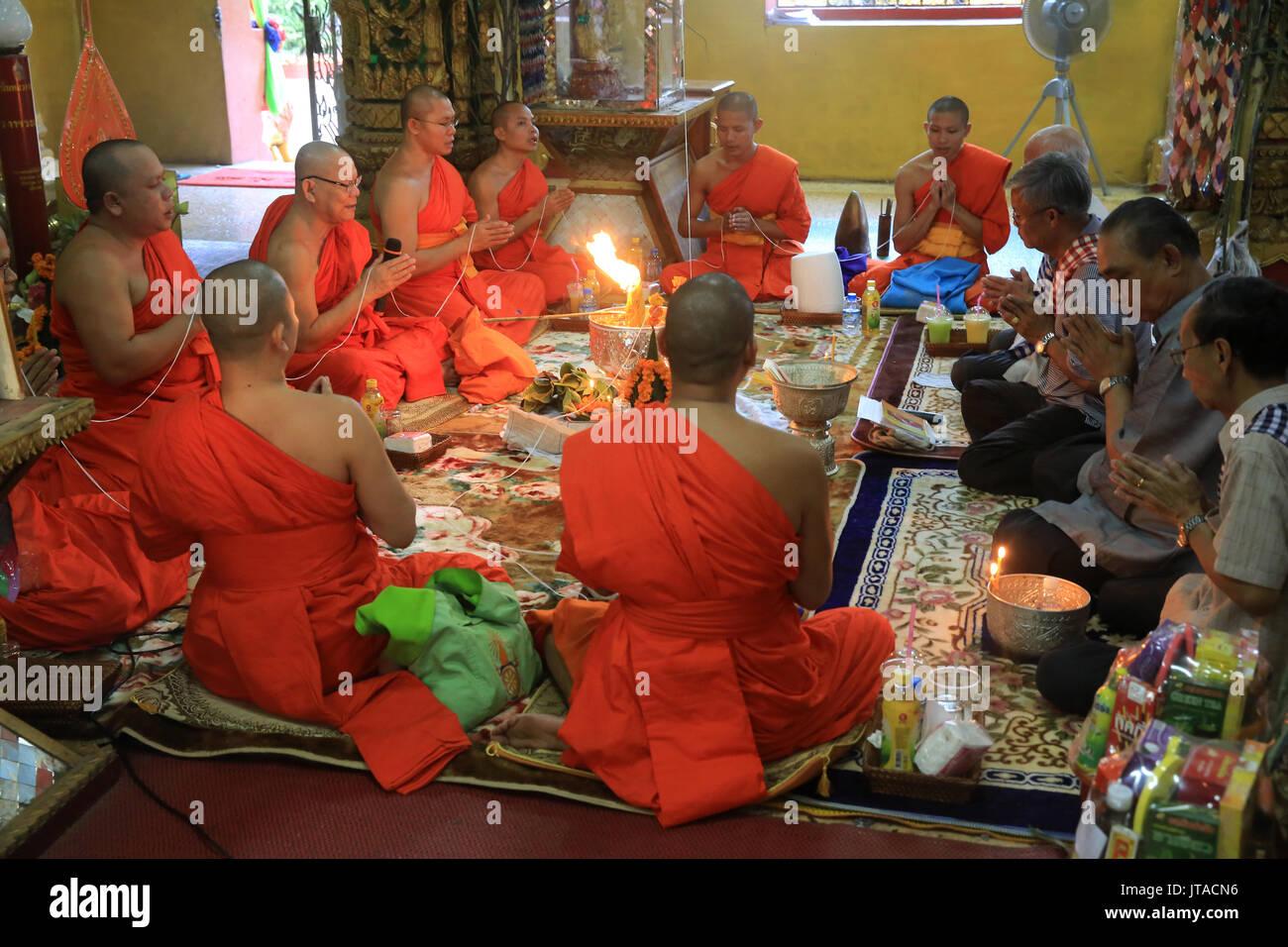 Les moines bouddhistes priant, Sai Sin, le fil de coton symbolisant le lien sacré, Simuong Wat (Wat Si Muang), Vientiane, Laos, Indochine, Asie du sud-est Photo Stock