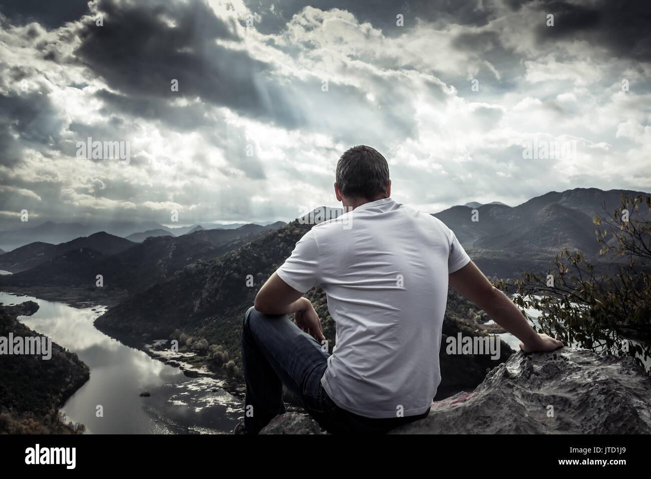 Homme seul à la recherche d'espoir à l'horizon sur sommet de montagne spectaculaire avec la lumière du soleil pendant le coucher du soleil avec effet de lumière au bout du tunnel Photo Stock