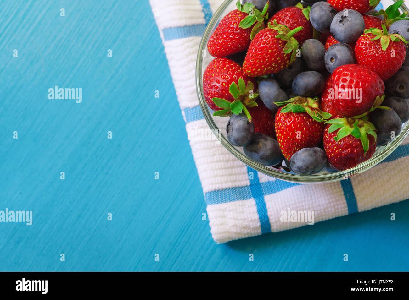 Bol en verre avec assortiment de petits fruits bleuets, fraises et des mûres au textile blanc plus de serviette de table en bois bleu. La lumière naturelle du jour. Top v Photo Stock