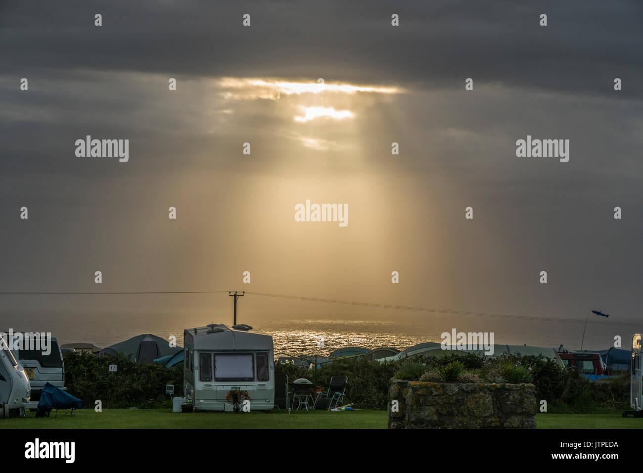 Briser les rayons à travers les nuages et illumine la mer à côté d'un camping à Sennen (près de Lands End), Penzance, Corwall, England, UK. Photo Stock