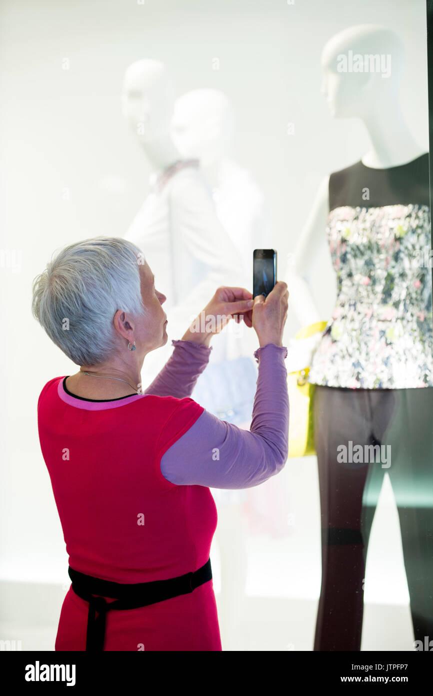 Femme plus âgée prend une photo de vêtements avec son téléphone portable Photo Stock