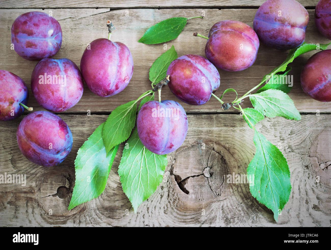 Les prunes violettes fraîches sur la table rustique en bois Banque D'Images