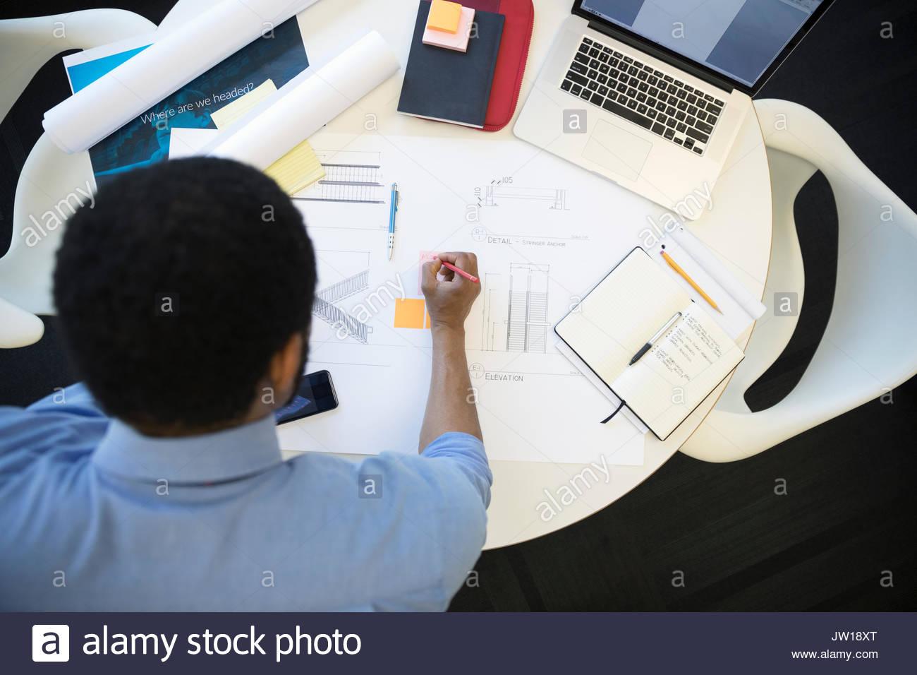Vue en plongée libre de la rédaction de plans à la table Photo Stock