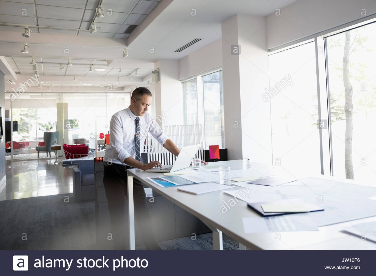 Architect working at laptop at table in open plan office Photo Stock