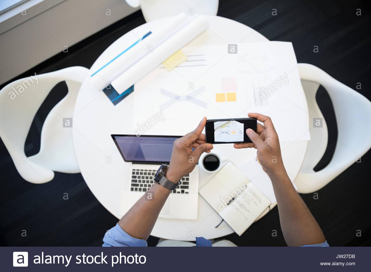 Vue de dessus avec l'architecte téléphone appareil photo photographier blueprints at table Photo Stock
