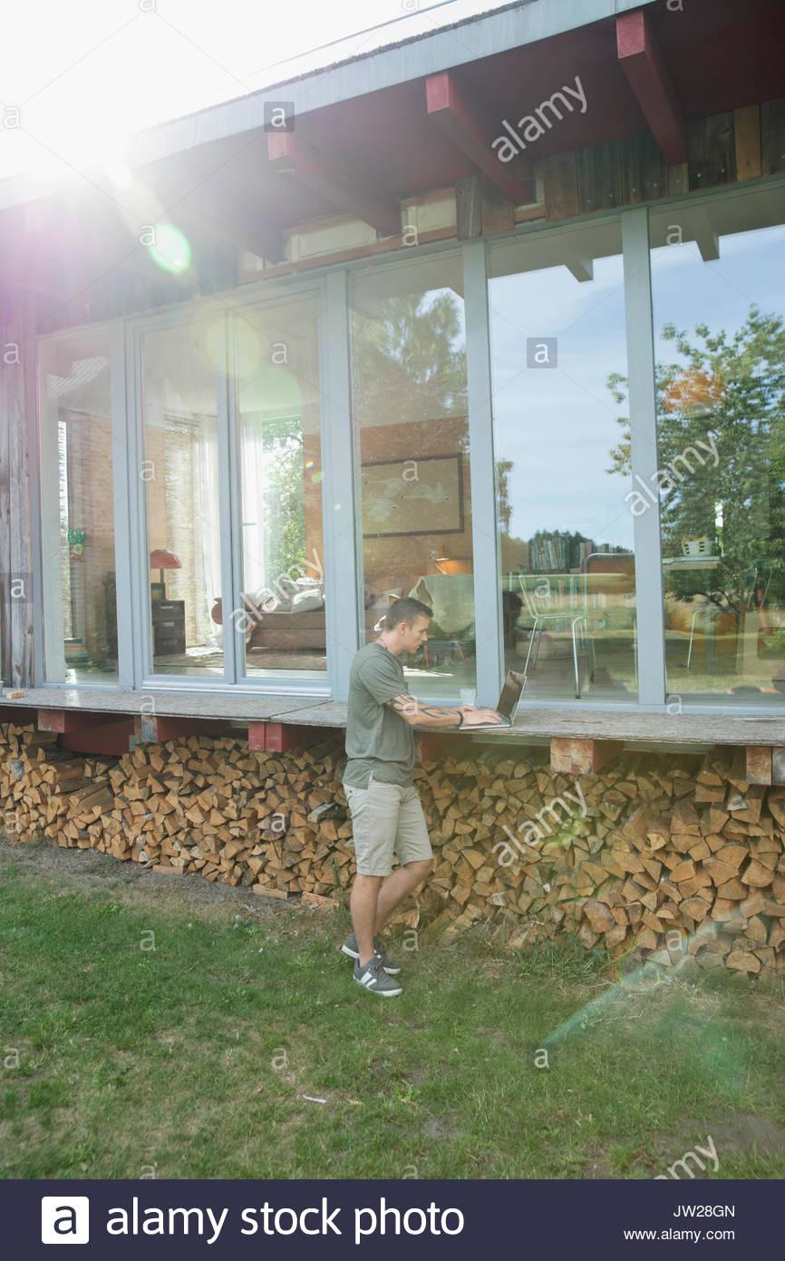 Young man using laptop on patio bois chalet bois ci-dessus Photo Stock