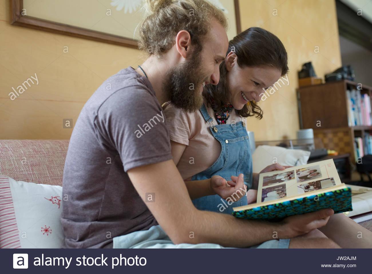 Couple à la recherche d'album en album photo sur salon canapé Photo Stock