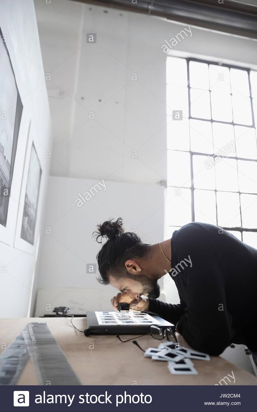 Photographe mâle examinant les diapositives avec loupe grossissante dans art studio Photo Stock