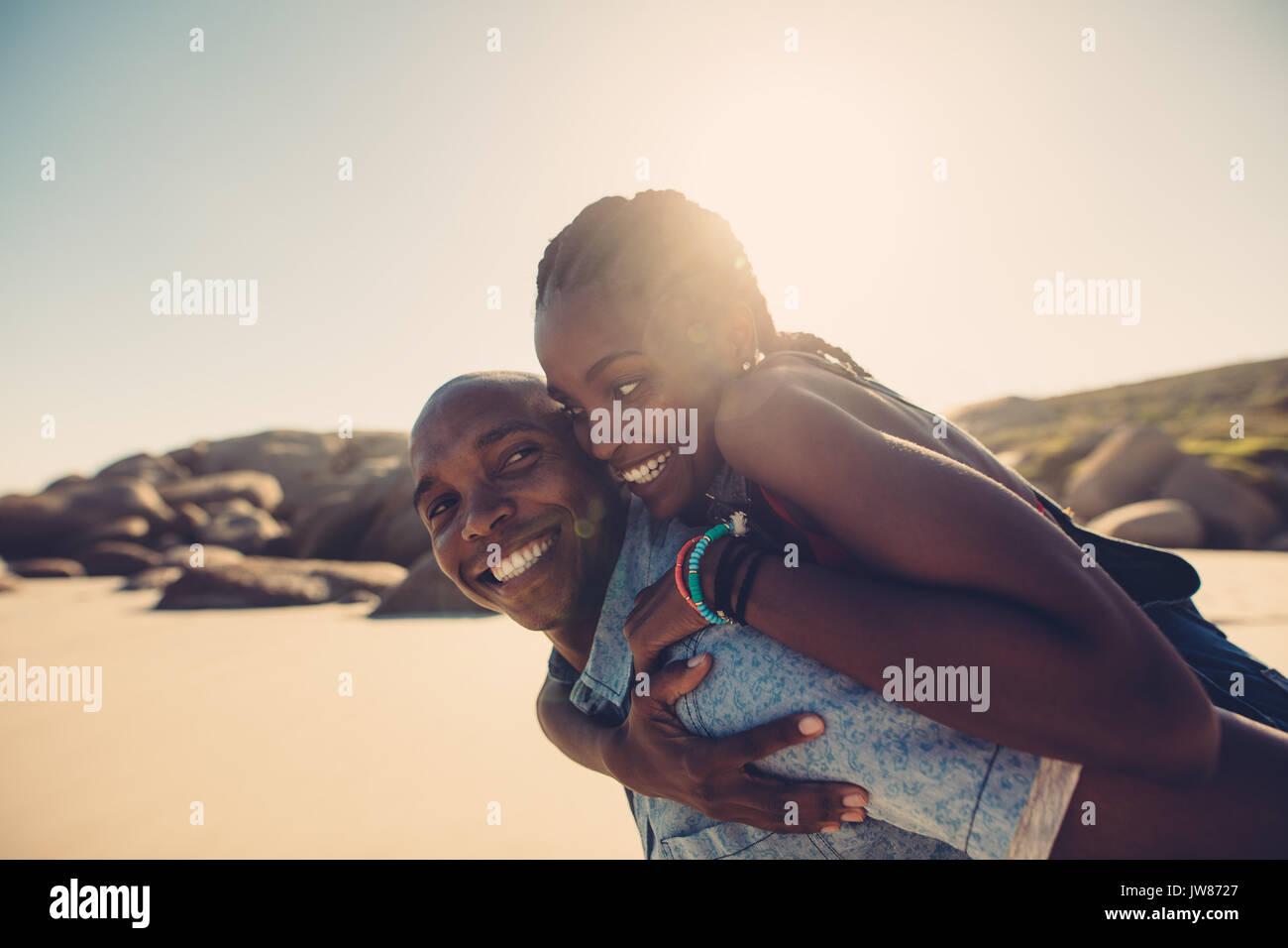 Couple de jeunes Africains sur le dos à la plage. Petit ami donnant piggyback ride à sa belle petite amie à seashore Banque D'Images