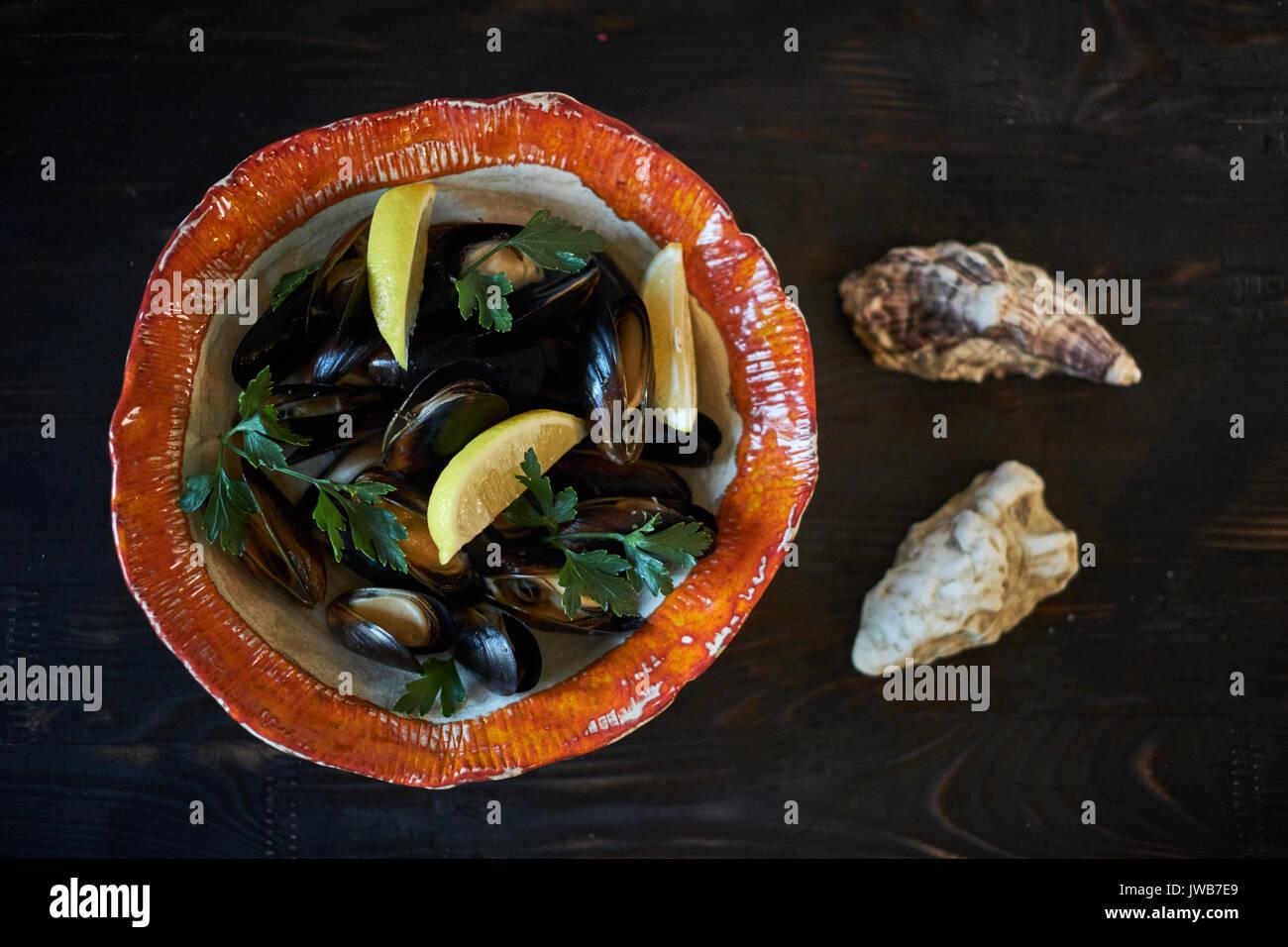 Les moules sur la glace prêt à cuire avec le citron et le vin blanc jpg Banque D'Images