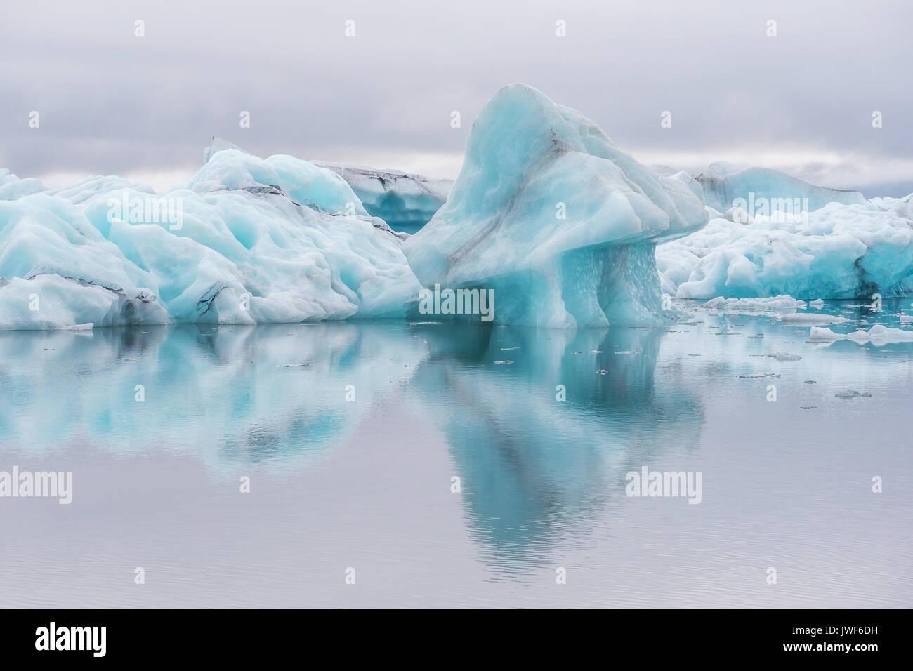 Les icebergs bleu flottant sur l'eau calme avec des réflexions Jokulsarlon glacier lagon. L'Islande. Photo Stock
