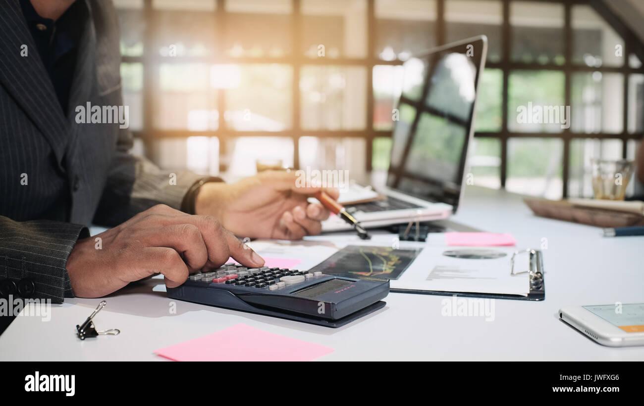 L'homme d'affaires finances calcul sur calculatrice de bureau dans un format 16:9. Photo Stock