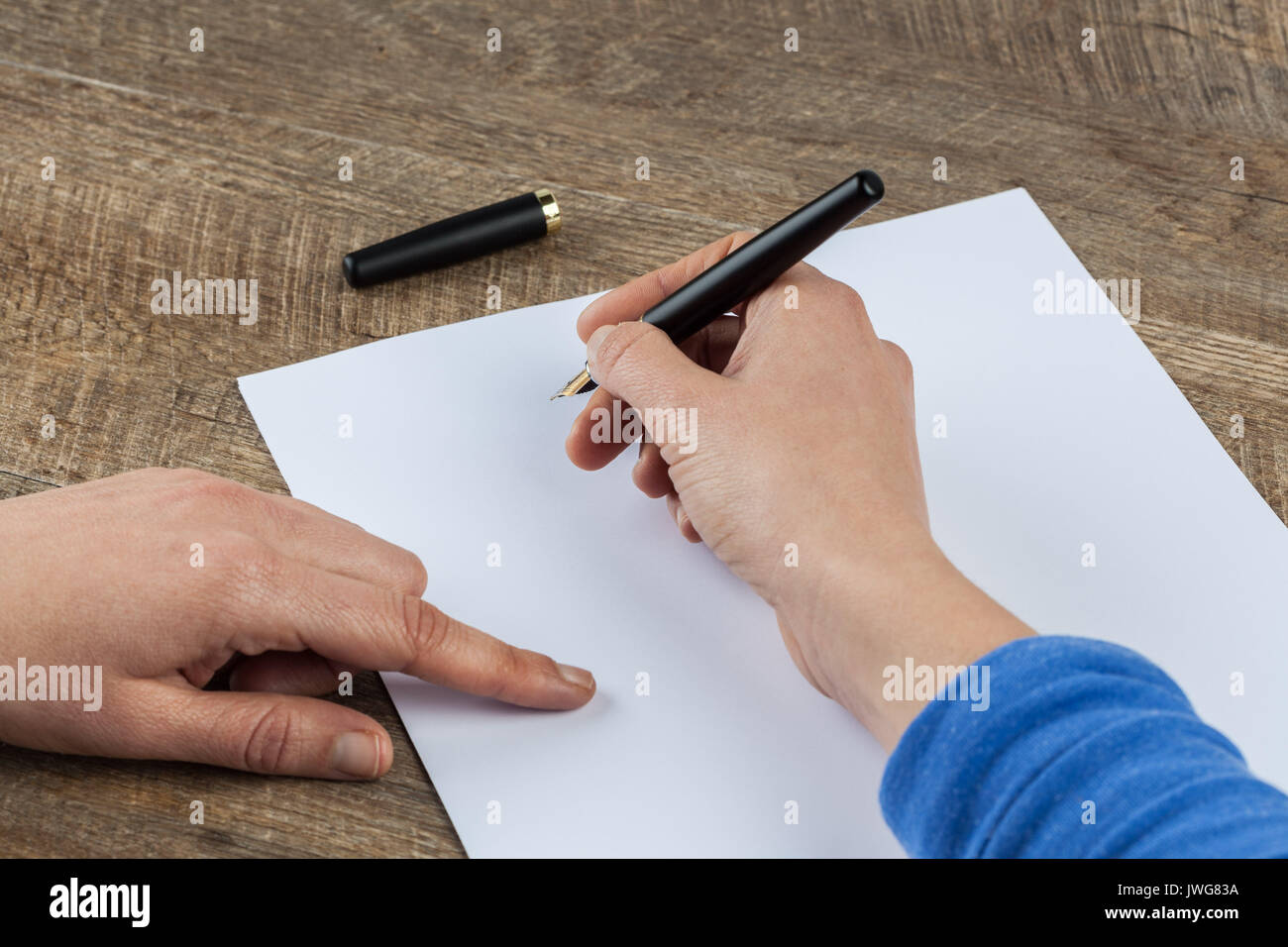 Femme hands holding stylo et feuille de papier blanc sur la table en bois Banque D'Images