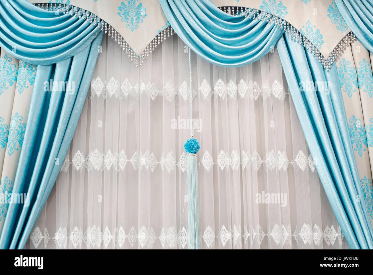 Partie de rideau drapé magnifiquement sur la fenêtre dans la chambre ...